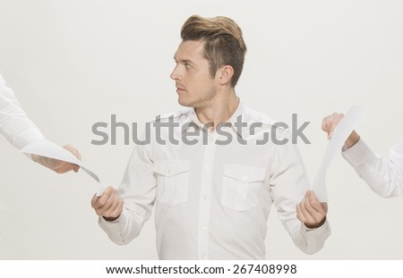 Young man taking two sheets of white paper from both side, isolated on white - stock photo