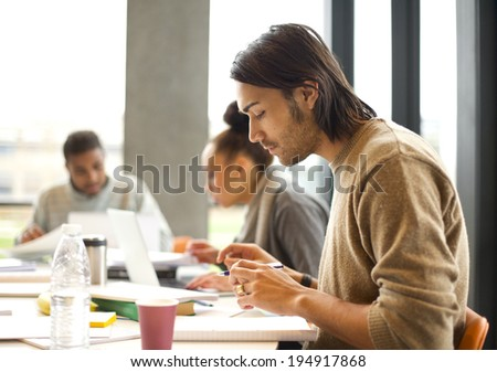 Young man talking notes for study with students studying in background. University students preparing for final exams in library. - stock photo