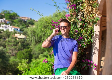 Young man talking on cellphone outdoors - stock photo