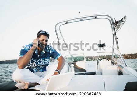 Young man talking on his cell phone and using a laptop on a boat - stock photo