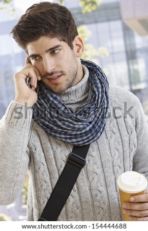 Young man talking on mobile phone in the city. - stock photo