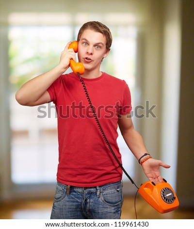 Young Man Talking On Retro Telephone, Indoors