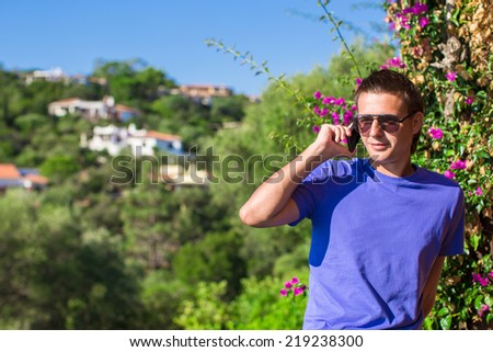 Young man talking on the phone at the balcony with beautiful view - stock photo