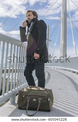 Young man talking on the phone over a bridge