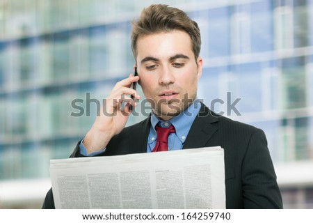 Young man talking on the phone while reading the newspaper