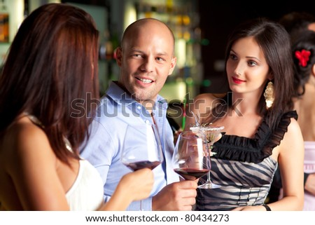young man talking to beautiful women at the bar - stock photo