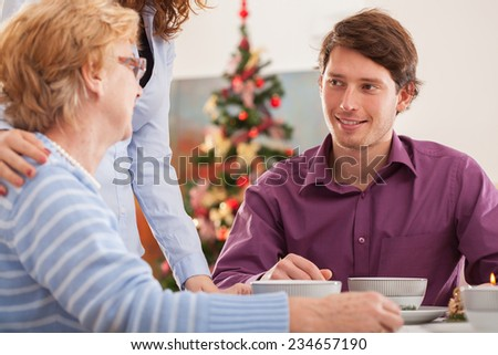 Young man talking with his grandmother during the Christmas dinner - stock photo