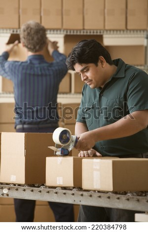 Young man taping a cardboard box closed - stock photo