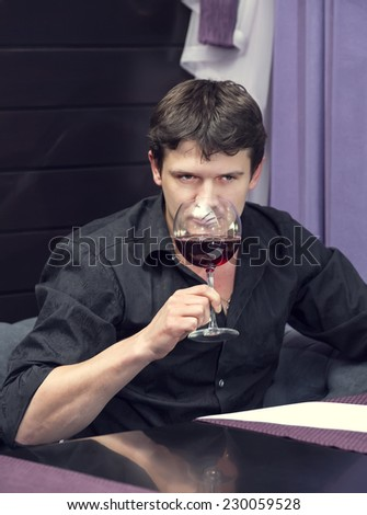 young man tasting wine at a table in a restaurant - stock photo