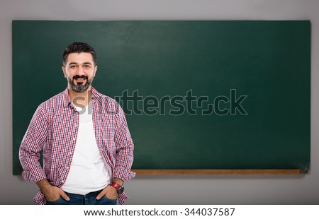 Young man teacher on green board.