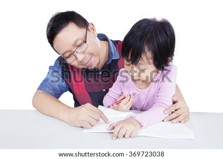 Young man teaching his daughter to study and doing homework, isolated on white background - stock photo