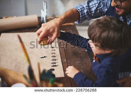 Young man teaching his son how to print on paper with help of potato and gouache - stock photo