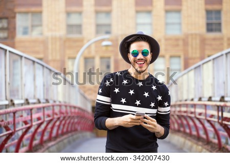 Young man texting on his smartphone on a urban background - stock photo