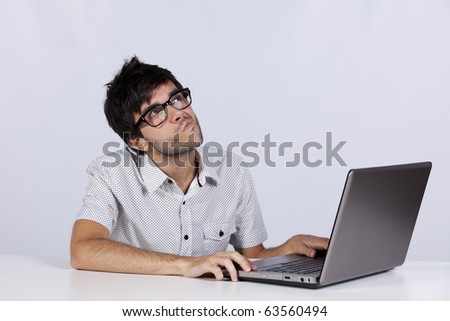 Young man thinking about a solution for a computer problem - stock photo