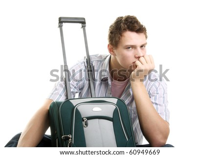 young man thinking near the suitcase in studio - stock photo