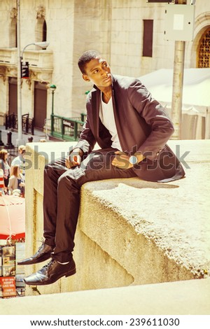 Young man thinking on street. A young black college student is sitting outside, arched the back, turning back, looking up, under strong sunshine, thinking. - stock photo