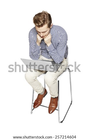 Young man thinking over the computer. He is sad.  - stock photo