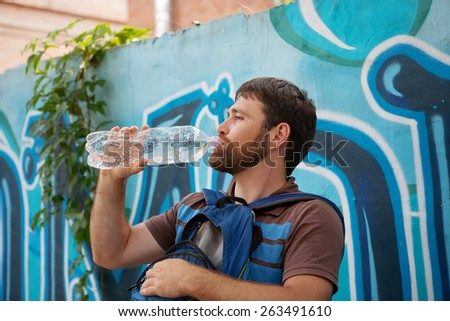 young man thirsty eagerly drinking water from clear plastic bottles on background with graffiti - stock photo