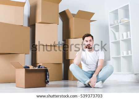 Young man thought sitting on the floor. Moving in house. New home concept.