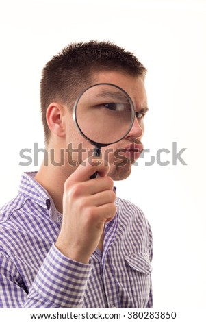 Young man through Magnifying glass, isolated on white