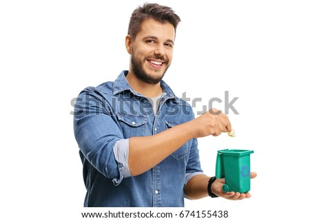 Young man throwing a piece of garbage in a small recycling bin isolated on white background
