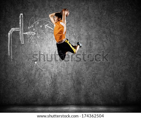 Young man throwing ball into basket in jump - stock photo