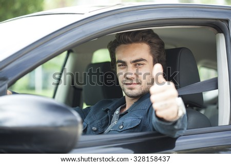 Young man thumbs up gesture in car