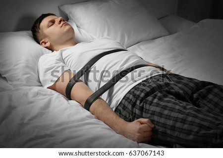 Young man tied up with belts in bed