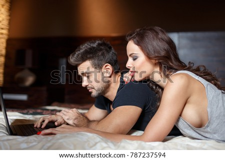 Young man tired about online shopping with wife by laptop on bed