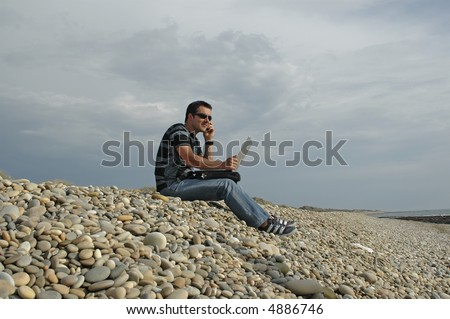 young man to the cellular one and with the computer in top of the legs, to the outdoors... - stock photo