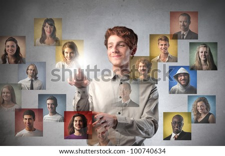 Young man touching icons of different people on a touchscreen - stock photo