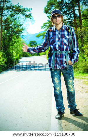Young man tourist hitchhiking along a road. - stock photo