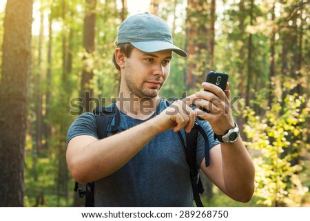Young man tourist looking maps on smartphone in forest.