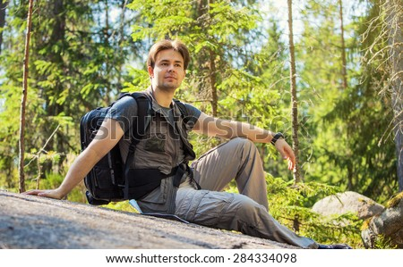 Young man tourist sitting on stone in summer forest. - stock photo