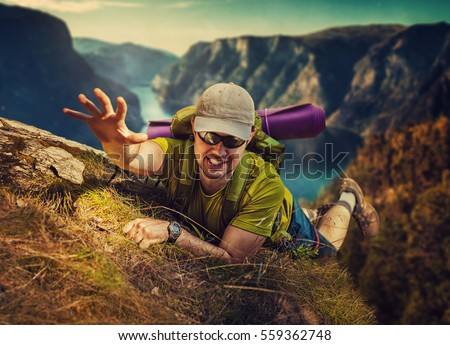 Young man tourist surviving falling from high mountain and trying to climb up