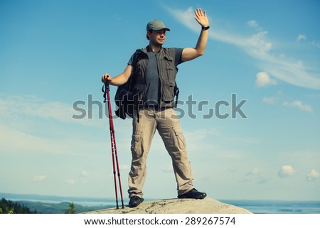 Young man tourist with backpack and sticks standing on mountain top and waving hand. - stock photo