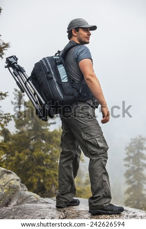 Young man tourist with backpack and tripod standing on mountain top at rainy weather. - stock photo