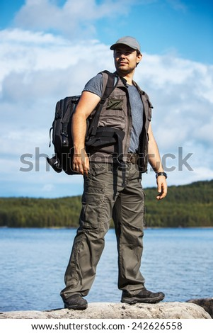 Young man tourist with backpack standing on rock on lake background.