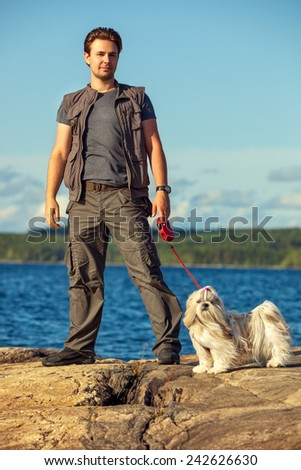 Young man tourist with shih-tzu dog walking on lake shore. - stock photo