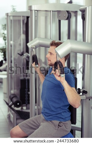 Young man training in a gym doing a workout to tone and strengthen his muscles with counter weighted equipment in a health, exercise and fitness concept - stock photo
