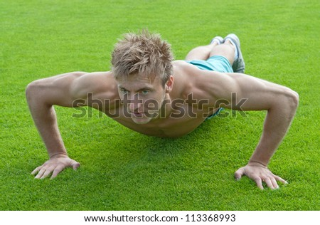 Young man training outdoors and doing push-ups on green grass.