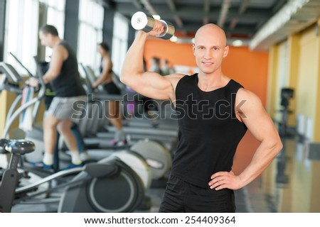 Young man training with dumbbells at the gym