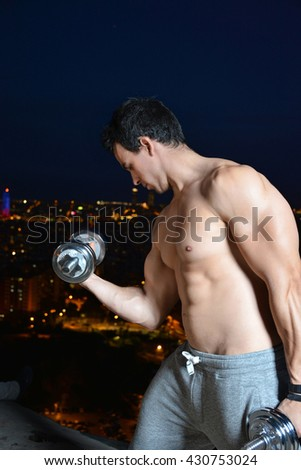 young man training with dumbbells on top of a viewpoint of a city