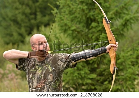 Young man training with the bow  - stock photo