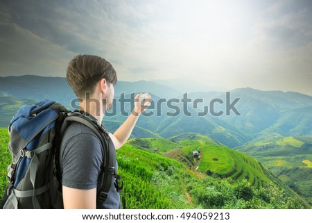 Young Man Traveler holding compass and backpack relaxing outdoor with Rice fields on terraced of Mu Cang Chai, YenBai, Vietnam. Rice fields prepare the harvest at Northwest Vietnam.Vietnam landscapes.