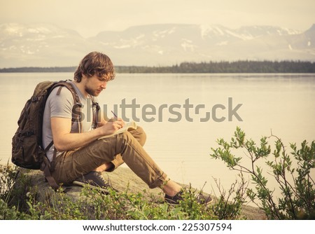 Young Man Traveler with backpack reading book and writing notes outdoor mountains on background Summer vacations and Lifestyle concept - stock photo