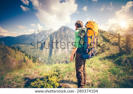 Young Man Traveler with backpack relaxing outdoor with rocky mountains on background Summer vacations and Lifestyle hiking concept - stock photo