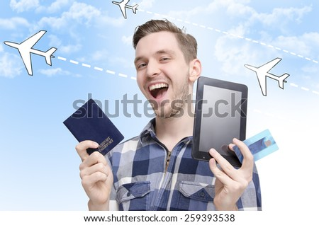 Young man traveling concept, smiling while holding tablet, passport and credit cards, booking flights via tablet online and traveling around the world. Graphic planes in background - stock photo