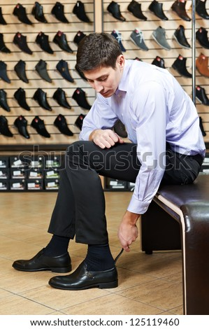 Young man trying on new shoes during footwear shopping at shoe shop - stock photo