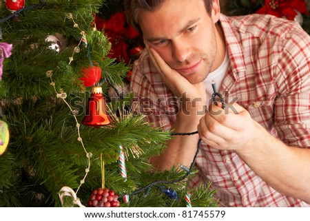 Young man trying to fix Christmas tree lights - stock photo